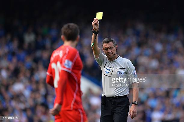 Referee Andre Marriner shows Liverpool's English midfielder Adam Lallana the yellow warning card during the English Premier League football match...