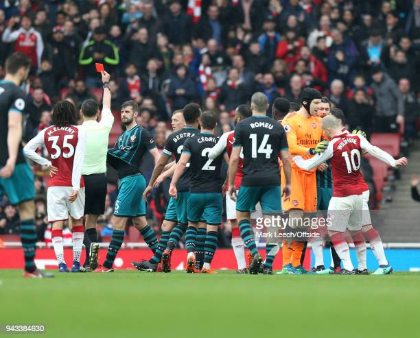 Referee Andre Marriner shows the red card to Jack Stephens of Southampton as Arsenal goalkeeper Petr Cech holds back Jack Wilshere of Arsenal during...