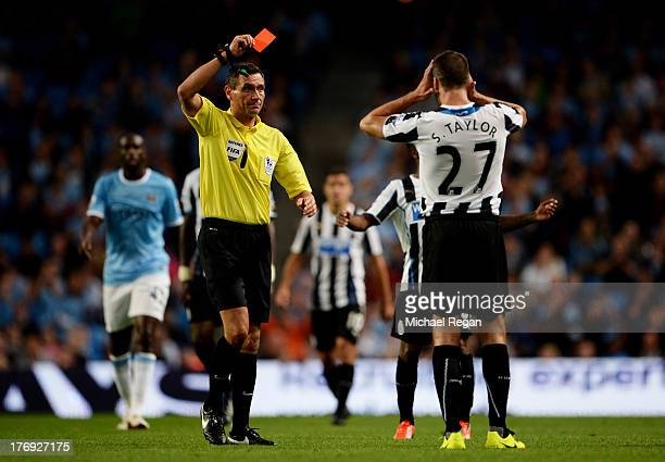Referee Andre Marriner shows the red card to Steven Taylor of Newcastle United during the Barclays Premier League match between Manchester City and...