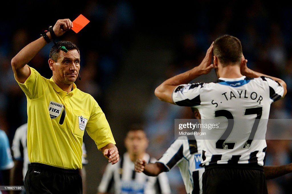Referee Andre Marriner shows the red card to Steven Taylor of Newcastle United during the Barclays Premier League match between Manchester City and Newcastle United at the Etihad Stadium on August 19, 2013 in Manchester, England.