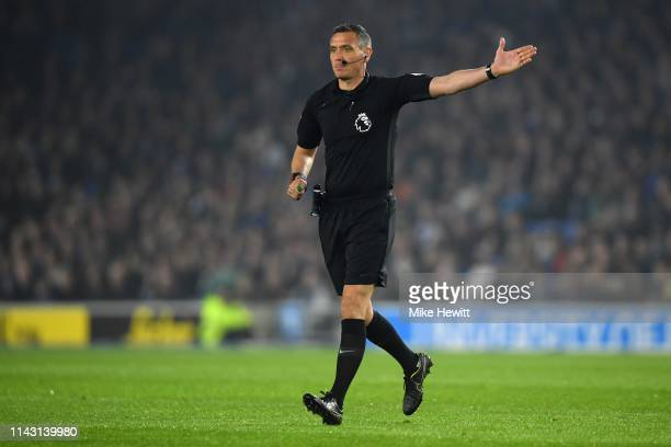 Referee Andre Marriner signals during the Premier League match between Brighton Hove Albion and Cardiff City at American Express Community Stadium on...