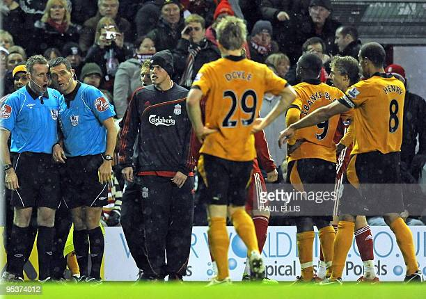 Referee Andre Marriner speaks to his assistant before sending off Wolverhampton Wanderers' Irish defender Stephen Ward during the English Premier...