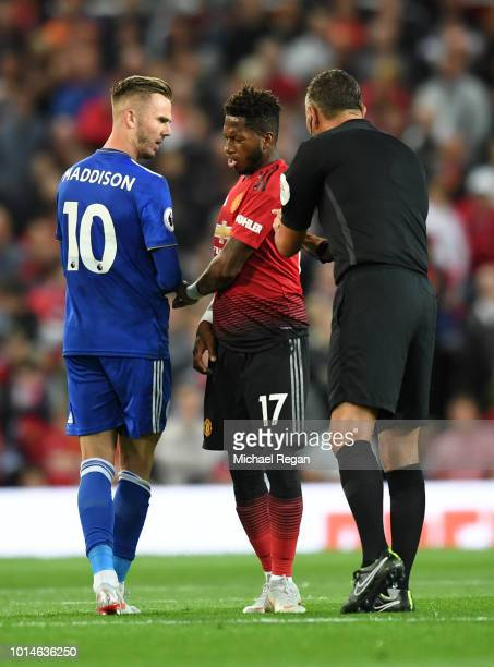 Referee Andre Marriner speaks to James Maddison of Leicester City and Fred of Manchester United during the Premier League match between Manchester...