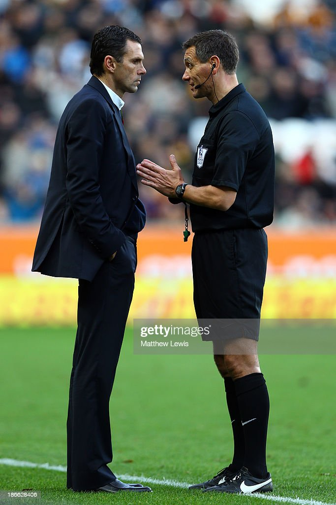 Referee Andre Marriner (R) speaks with Sunderland manager Gus Poyet during the Barclays Premier League match between Hull City and Sunderland at KC Stadium on November 2, 2013 in Hull, England.