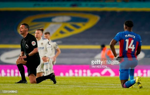 Referee Andre Marriner takes the knee in support of the No Room For Racism campaign during the English Premier League football match between Leeds...