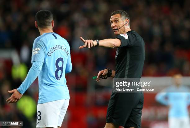 Referee Andre Marriner takes to Ilkay Gundogan of Manchester City during the Premier League match between Manchester United and Manchester City at...