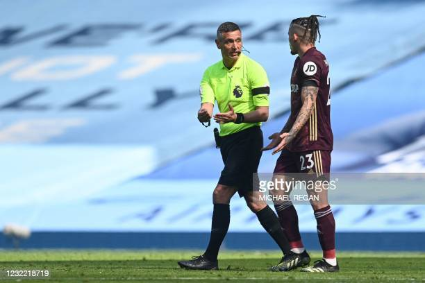 Referee Andre Marriner talks to Leeds United's English midfielder Kalvin Phillips during the English Premier League football match between Manchester...