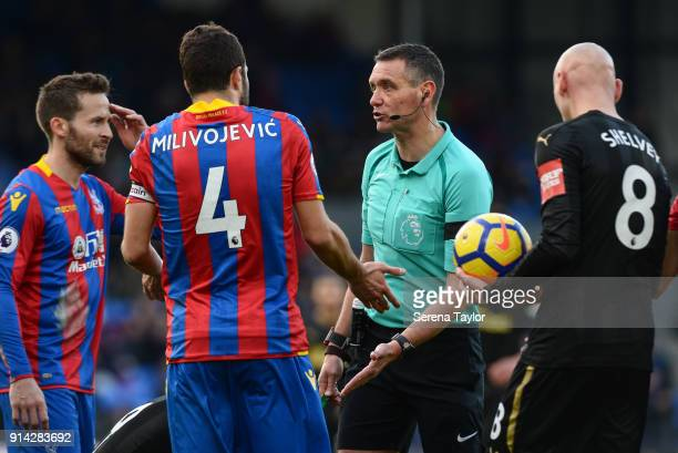 Referee Andre Marriner talks to Yohan Cabaye and Luka Milivojevic of Crystal Palace during the Premier League match between Crystal Palace and...