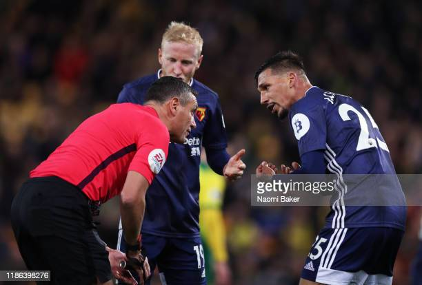 Referee Andre Marriner talks with Will Hughes and Jose Holebas of Watford during the Premier League match between Norwich City and Watford FC at...