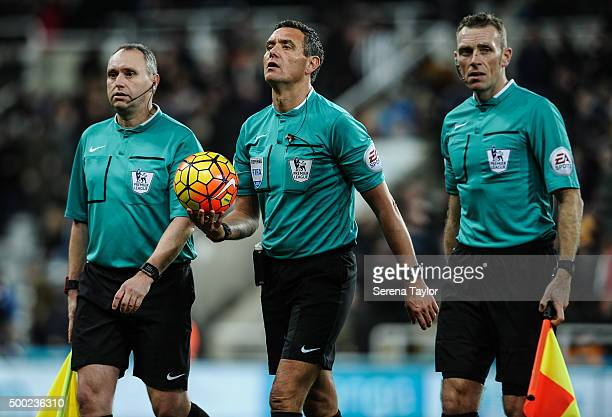 Referee Andre Marriner walks off the pitch with assistant referees Darren Cann and Scott Ledger during the Barclays Premier League match between...