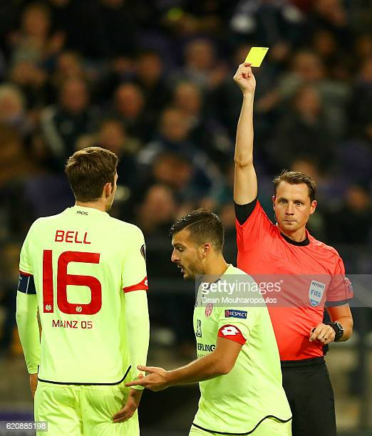 Referee Andreas Ekberg shows a yellow card to Giulio Donati of 1 FSV Mainz 05 during the UEFA Europa League Group C match between RSC Anderlecht and...