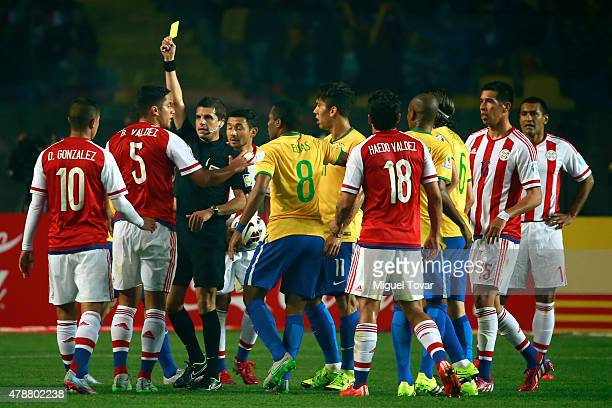 Referee Andres Cunha shows a yellow card to Bruno Valdez of Paraguay during the 2015 Copa America Chile quarter final match between Brazil and...