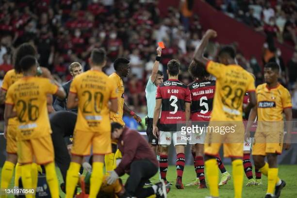 Referee Andrés Cunha shows a red card to Léo Pereira of Flamengo during a semi final first leg match between Flamengo and Barcelona SC as part of...