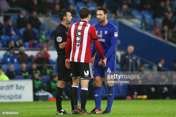 Referee Andy Madley calms both Sean Morrison of Cardiff City and Andreas Bjelland of Brentford after an altercation during the Sky Bet Championship...
