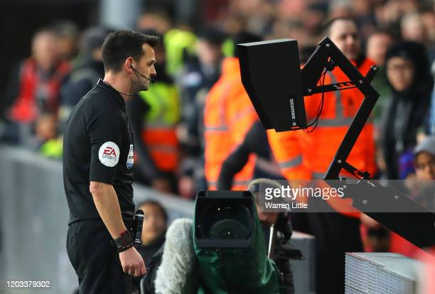 Referee Andy Madley checks the VAR screen during the Premier League match between Crystal Palace and Sheffield United at Selhurst Park on February 01...