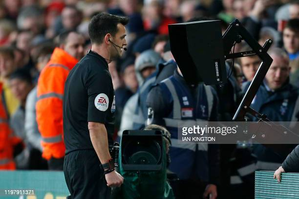 Referee Andy Madley checks the VAR screen to review his red card decision against Crystal Palace's English defender Joel Ward, for his challenge on...