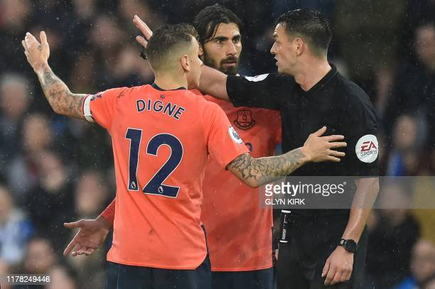 Referee Andy Madley waves away the protests of Everton's French defender Lucas Digne and Everton's Portuguese midfielder André Gomes after he awarded...