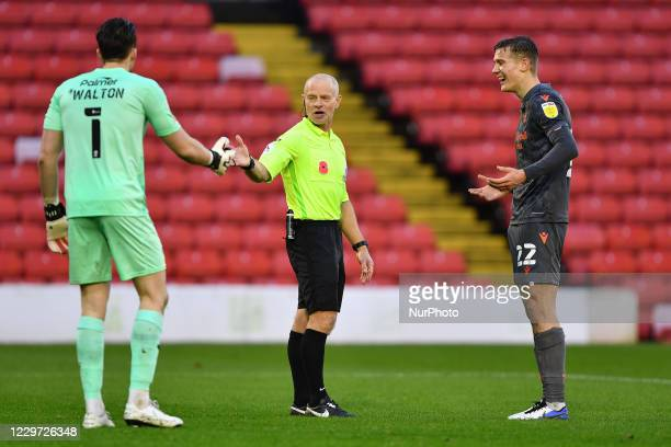 Referee Andy Woolmer has words with Jack Walton of Barnsley while Ryan Yates of Nottingham Forest finds it amusing during the Sky Bet Championship...