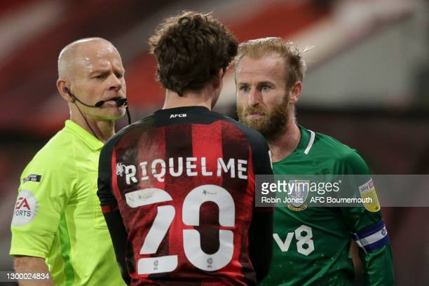 Referee Andy Woolmer looks on as Rodrigo Riquelme of Bournemouth and Barry Bannan of Sheffield Wednesday square up to each other during the Sky Bet...