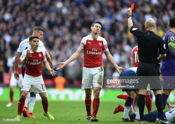 Referee Anthony Taylor awards Lucas Torreira of Arsenal a red card during the Premier League match between Tottenham Hotspur and Arsenal FC at...