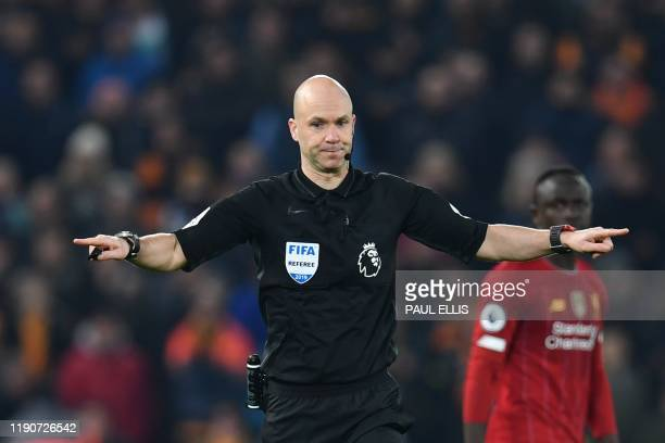 Referee Anthony Taylor gestures to have a VAR decision after Wolverhampton Wanderers' Portuguese midfielder Pedro Neto put the ball in the net during...