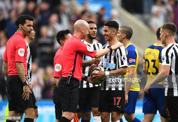 Referee Anthony Taylor gives Ayoze Perez of Newcastle United the match ball following his hattrick during the Premier League match between Newcastle...