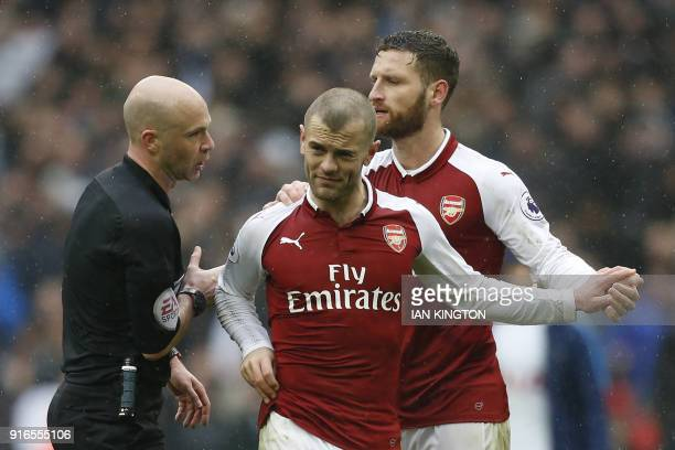 Referee Anthony Taylor has words with Arsenal's English midfielder Jack Wilshere as Arsenal's German defender Shkodran Mustafi shepherds him away at...