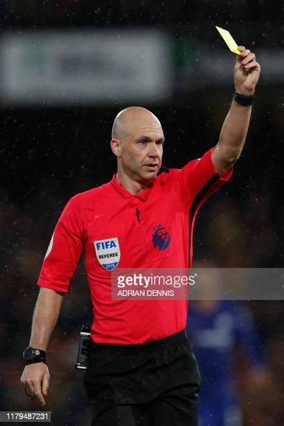 Referee Anthony Taylor produces a yellow card during the English Premier League football match between Watford and Chelsea at Vicarage Road Stadium...