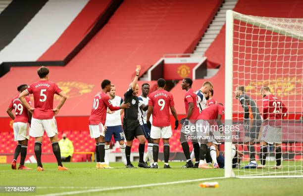 Referee Anthony Taylor shows a red card to Anthony Martial of Manchester United during the Premier League match between Manchester United and...
