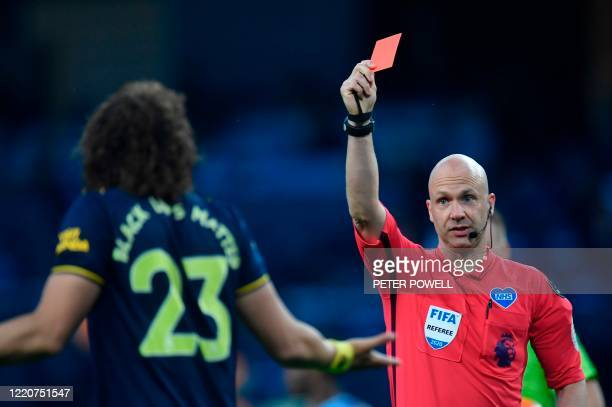 Referee Anthony Taylor shows a red card to Arsenal's Brazilian defender David Luiz during the English Premier League football match between...
