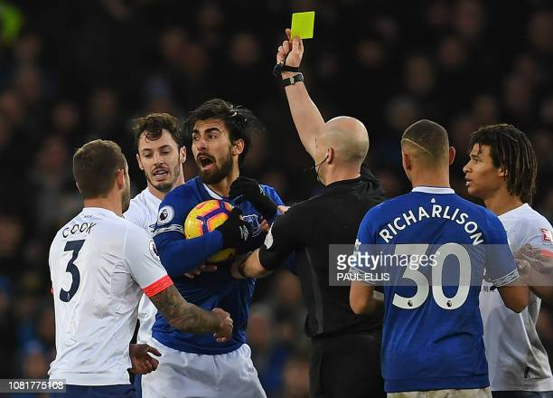 Referee Anthony Taylor shows a yellow card to Everton's Portuguese midfielder André Gomes during the English Premier League football match between...