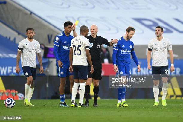Referee, Anthony Taylor shows Fernandinho of Manchester City a yellow card for a foul on James Maddison of Leicester City during the Premier League...