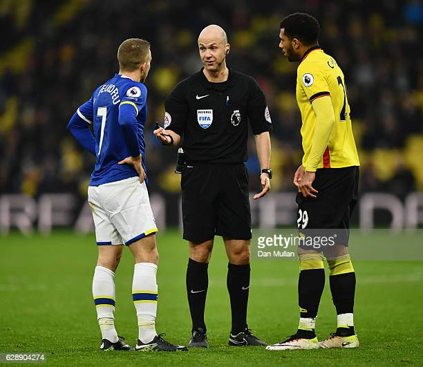 Referee Anthony Taylor talks to Gerard Deulofeu of Everton and Etienne Capoue of Watford as they clash during the Premier League match between...