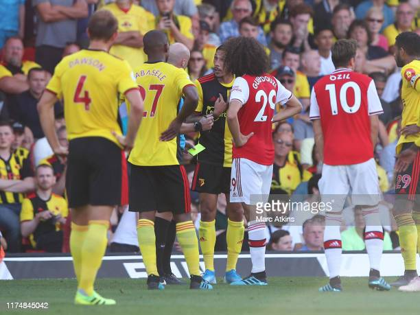 Referee Anthony Taylor talks to Jose Holebas of Watford and Matteo Guendouzi of Arsenal during the Premier League match between Watford FC and...