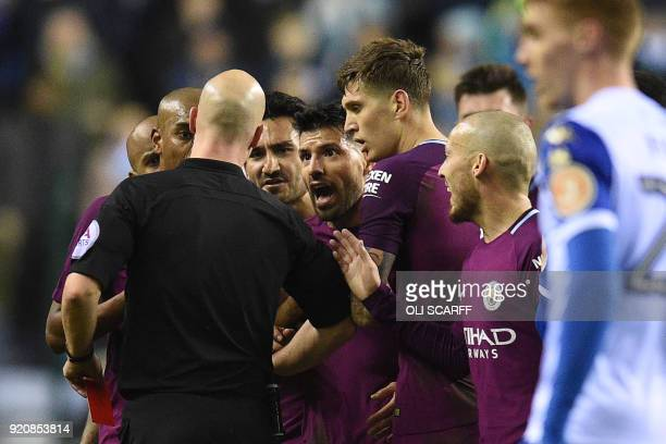 Referee Anthony Taylor talks to Manchester City players after giving a red card to Manchester City's English midfielder Fabian Delph during the...