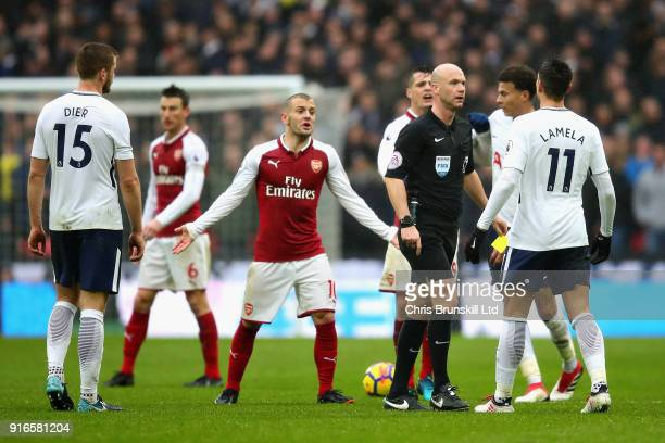 Referee Anthony Taylor talks with Erik Lamela of Tottenham Hotspur as Jack Wilshere of Arsenal reacts during the Premier League match between...