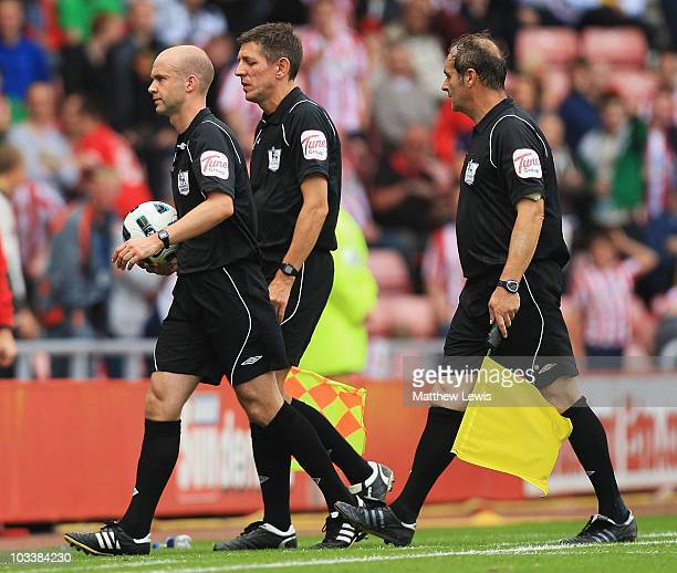 Referee Anthony Taylor walks off with his linesmen during the Barclays Premier League match between Sunderland and Birmingham City at the Stadium of...