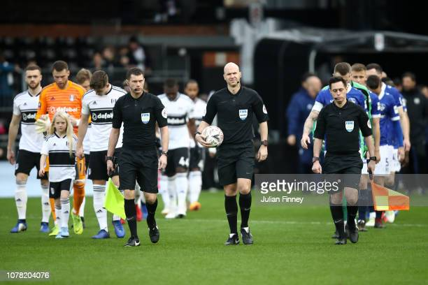 Referee Anthony Taylor walks out with the assistant referees Simon Bennett and Gary Beswick during the FA Cup Third Round match between Fulham and...
