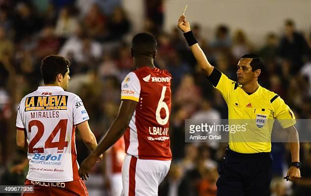 Referee Antonio Arias shows a yellow card to Leyvin Balanta of Santa Fe during a first leg final match between Huracan and Independiente Santa Fe as...