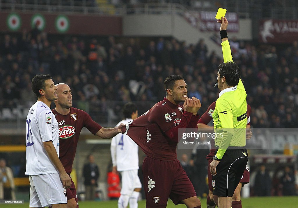 Referee Antonio D'Amato shows the yellow card to Danilo D'Ambrosio of Torino FC during the Serie A match between Torino FC and ACF Fiorentina at Stadio Olimpico di Torino on November 25, 2012 in Turin, Italy.