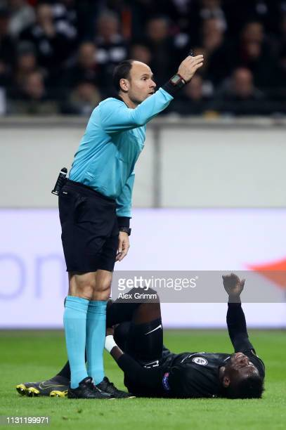 Referee Antonio Mateu Lahoz calls for medical assistance for Danny Da Costa of Eintracht Frankfurt during the UEFA Europa League Round of 32 Second...