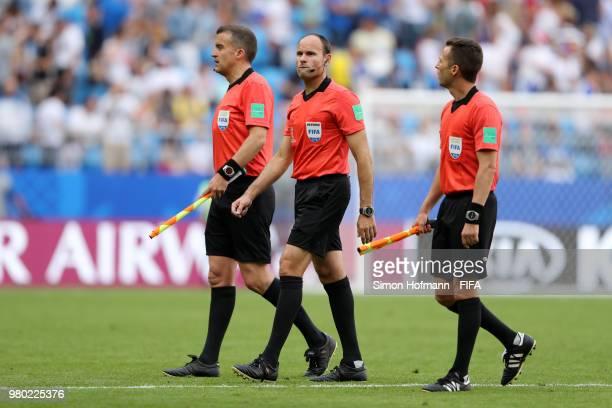 Referee Antonio Mateu Lahoz linesman Roberto Diaz Perez Del Palomar and linesman Pau Cebrian Devis walk on the pitchduring the 2018 FIFA World Cup...