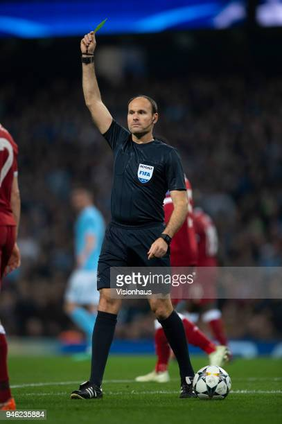 Referee Antonio Mateu Lahoz of Spain hands out a yellow card during the UEFA Champions League quarter final 2nd leg tie between Manchester City and...