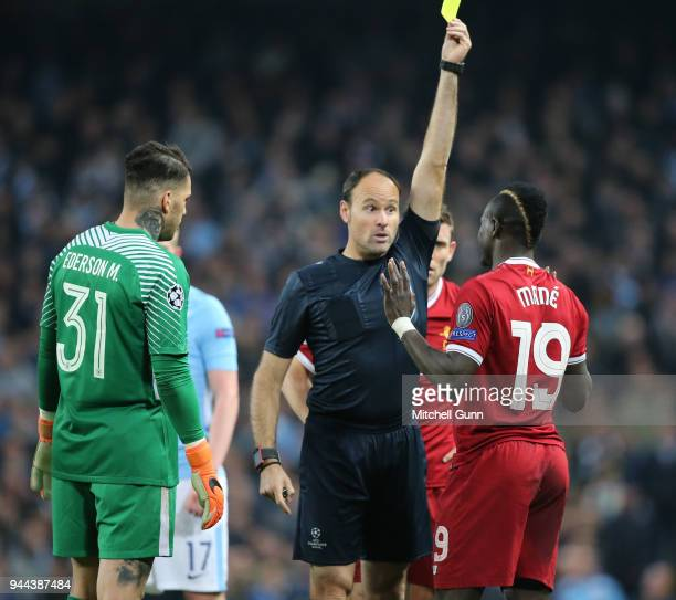 Referee Antonio Mateu Lahoz shows a yellow card to Sadio Mane of Liverpool and Ederson of Manchester City during the Champions League quarter final...
