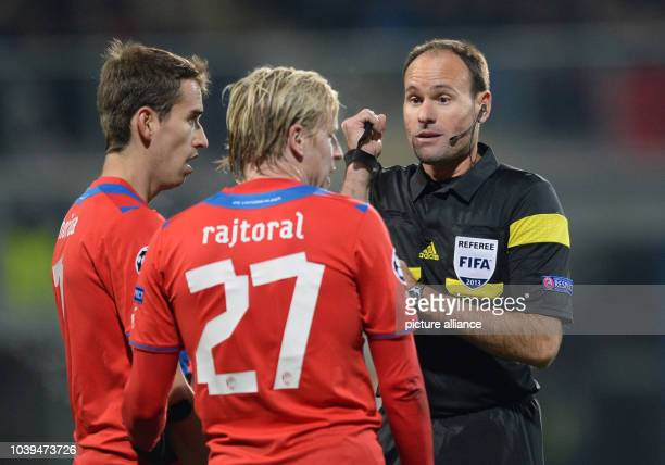 Referee Antonio Mateu Lahoz talks to Plzen's Frantisek Rajtoral and Tomas Horava during the UEFA Champions League Group D soccer match between FC...