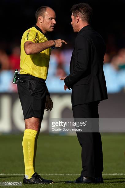 Referee Antonio Mateu Lahoz talks with Diego 'Cholo' Simeone the manager of Atletico de Madrid during the La Liga match between RC Celta de Vigo and...