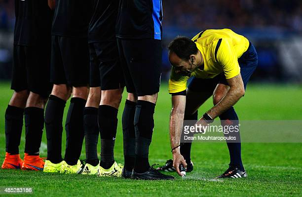 Referee Antonio Mateu Lahoz uses vanishing spray during the UEFA Champions League qualifying round play off 2nd leg match between Club Brugge and...