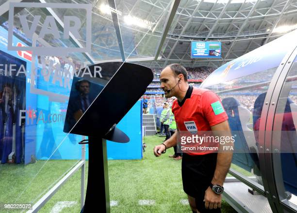 Referee Antonio Mateu reviews the VAR footage before awarding Australia a penalty during the 2018 FIFA World Cup Russia group C match between Denmark...