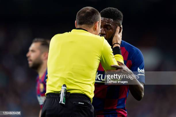 referee Antonio Miguel Mateu Lahoz and Samuel Umtiti of FC Barcelona gesture during the Liga match between Real Madrid CF and FC Barcelona at Estadio...