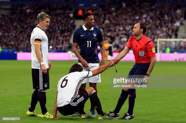 Referee Antonio Miguel Mateu Lahoz helps up Germany's Sami Khedira as France's Anthony Martial and Germany's Bastian Schweinsteiger look on